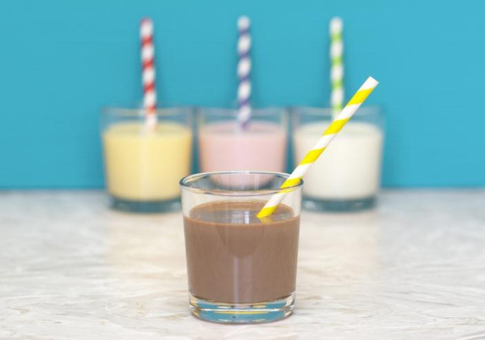 Chocolate milkshake in front of a row of flavoured milkshakes